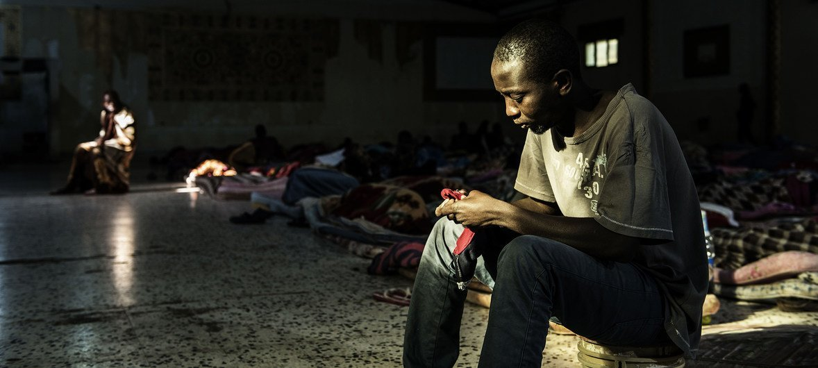 A migrant sits in a patch of light entering through one of only two windows as he tries to warm himself up at a detention centre, located in Libya, 1 February 2017. At the time of UNICEF's visit, 160 men were being detained there.