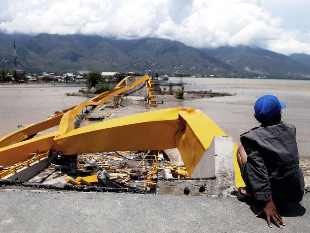 Un homme regarde une route et un pont détruits dans la ville de Palu sur l'île indonésienne de Sulawesi frappée par un séisme et un tsunami en septembre 2018. Plus de 2 000 personnes sont mortes et 80 000 ont été déplacées.