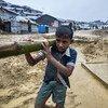 Au Bangladesh, un garçon transporte du bambou sur une route boueuse menant au camp de Balukali à Cox's Bazar. En prévision de la mousson, d'importantes quantités de bambou ont été réquisitionnées pour renforcer les abris.