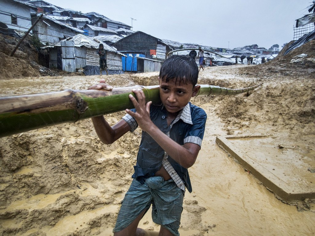 在孟加拉国的考克斯巴扎地区,一名男孩扛着竹子艰难行走在难民营中泥泞的道路上。