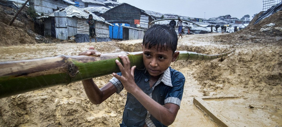 A boy carries bamboo along a very muddy road into the Balukali camp in Cox's Bazar, Bangladesh.  In preparation for the monsoon season, a frenzy of building and reinforcement required vast quantities of bamboo.  13 June 2018.