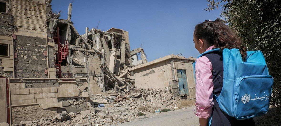 Una niña camina hacia la escuela en medio de edificios destruidos por la guerra en Iraq.