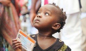 Une petite fille tenant une carte de vote lors des élections de 2011 en République démocratique du Congo (RDC).