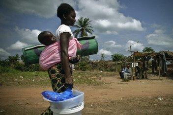 Une réfugiée de la République démocratique du Congo (RDC) porte son enfant ainsi que des articles de secours au Congo-Brazzaville.   © HCR / Frederic Noy