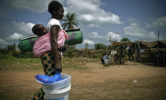 A refugee mother carries her child and relief items in Congo-Brazzaville. (file)