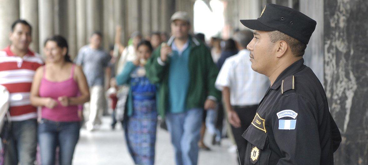 一名警察在危地马拉城的一个贸易区巡逻资料图片。