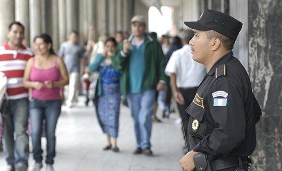 Сотрудник Национальной гражданской полиции патрулирует торговый район в Гватемале