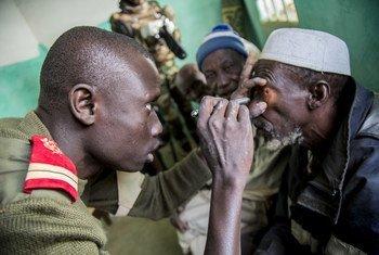 Mlinda amani  wa UN  kutoka Senegal akichunguza jicho la mkazi wa wanavijiji huko Mopti, nchini Mali.