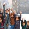 Des enfants afghans montrent leurs doigts marqués pour indiquer qu'ils ont été vaccinés contre la poliomyélite.