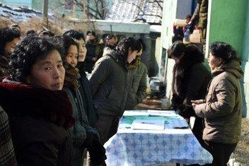 2017年1月26日,在朝鲜松川县,一名妇女正在排队领取分发的食品。