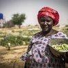 Une femme au Mali avec des légumes qu'elle a récoltés.