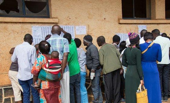 Eleitores procuram os seus nomes nas listas durante as eleições presidenciais e legislativas em dezembro passado.