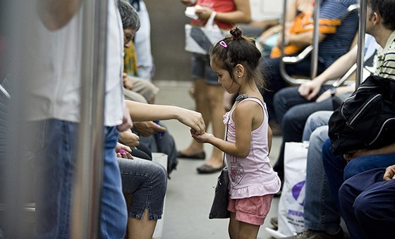 Five-year-old Kiara makes a sale in a commuter train car in Buenos Aires, the capital. She has been working in the Subte, the city's mass transit system, selling hairpins and other cheap goods, since she was three years old.