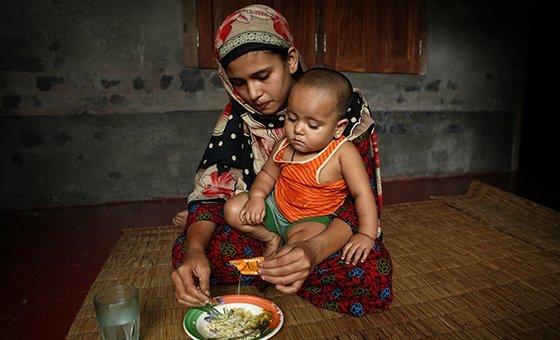 Sonamoni, de 13 anos, alimenta sua filha de 11 meses. Ela tinha 8 anos quando se casou com o marido, que agora tem 29 anos.