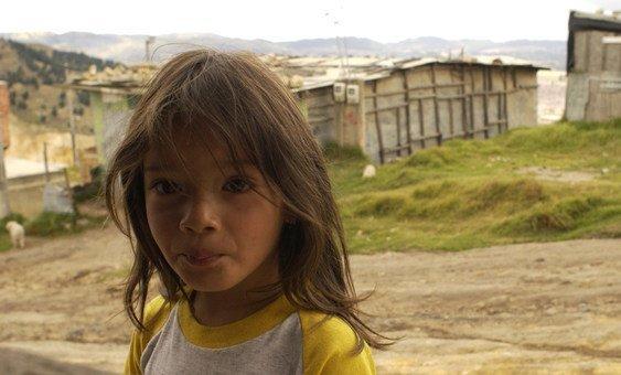 Una niña de 5 años frente al pequeño supermercado de sus padres en el empobrecido barrio de Altos de Cazucá , en el municipio de Soacha, en las afueras de Bogotá, Colombia.