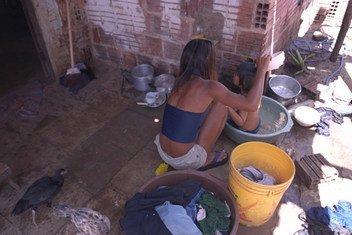Susana, de 14 años, baña a su pequeño sobrino detrás de su vivienda en un barrio pobre de una gran ciudad brasileña. La pobreza y la desigualdad obstaculizan el desarrollo social y sostenible en América Latina.