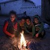 Children at Batbu camp in western rural Aleppo, Syria, burn pieces of cartons and paper to warm up at night. November 2018.