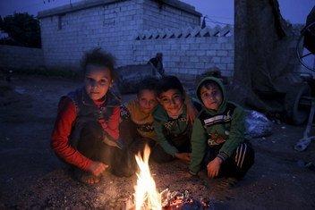 2018年11月的一个晚上,叙利亚阿勒颇西部农村一个营地的孩子们正在烧纸取暖。