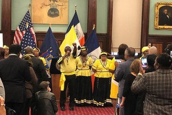A member of the Chief Joseph Chatoyer Dance Company, customed in the Garifuna traditional colors of yellow, black and white, sings the national anthem at an event celebrating Garifuna heritage at New York's City Hall.  2018.