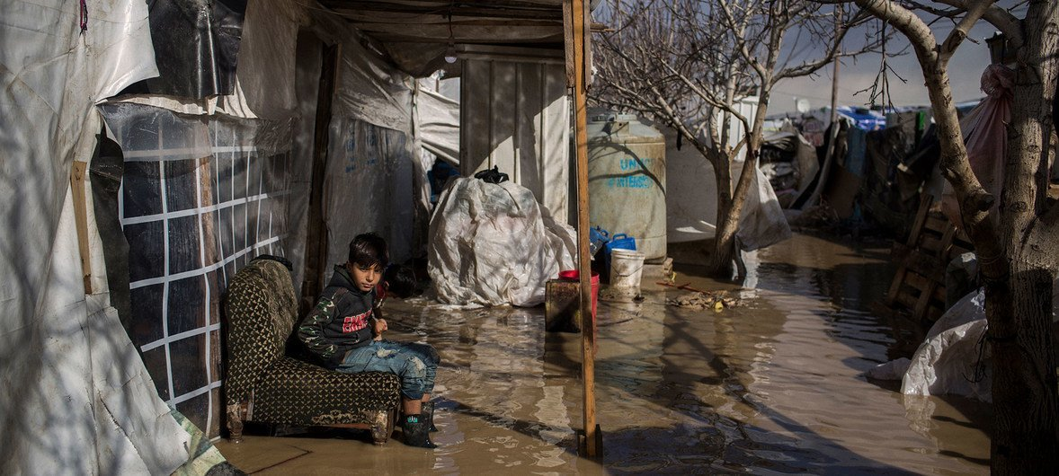 Nine-year-old Syrian refugee from Deir el Zor sits outside his flooded tent at Dalhamiya informal settlement camp in Lebanon. 9 January 2019.