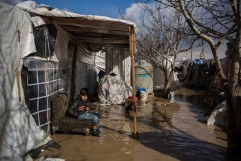 9 years old Syrian refugee from Deir el Zor sits sit outside his flooded tent at Dalhamiya informal settlement camp in Lebanon.  9 January 2019.