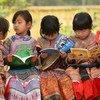 在越南偏远的老街省,土著社区的女孩们在小学校的户外一起读书。