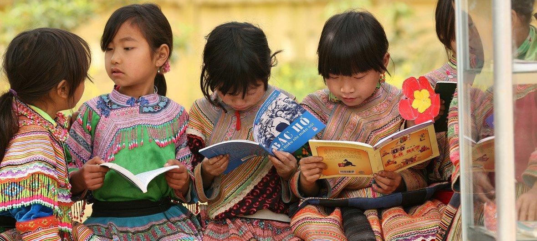 Девочки коренного населения читают на свежем водухе в провинции Лао Кай,Вьетнам.