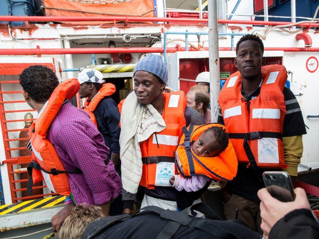 Un homme tenant dans ses bras un enfant débarque du navire Sea Watch à Malte le 9 janvier 2019.