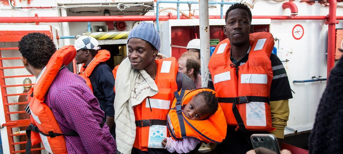 A man holding a one-year-old child disembarks from the Dutch-flagged rescue ship Sea Watch in Malta.  9 January 2019.