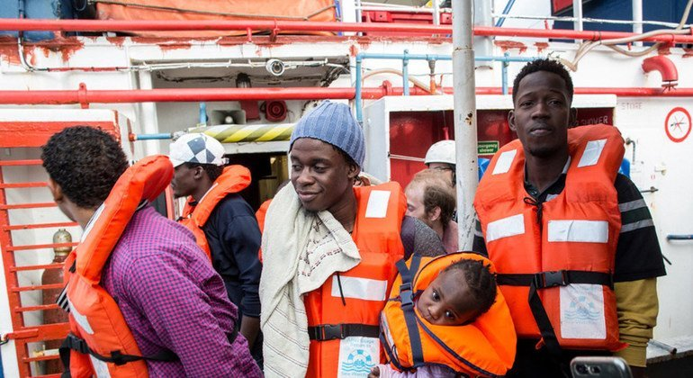 Un hombre sostiene a un niño de un año mientras desembarca de un buque de rescate con bandera holandesa.