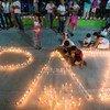 """来自哥伦比亚莫科阿(Mocoa)社区的妇女和儿童点燃蜡烛,组成""""和平""""字样。"""