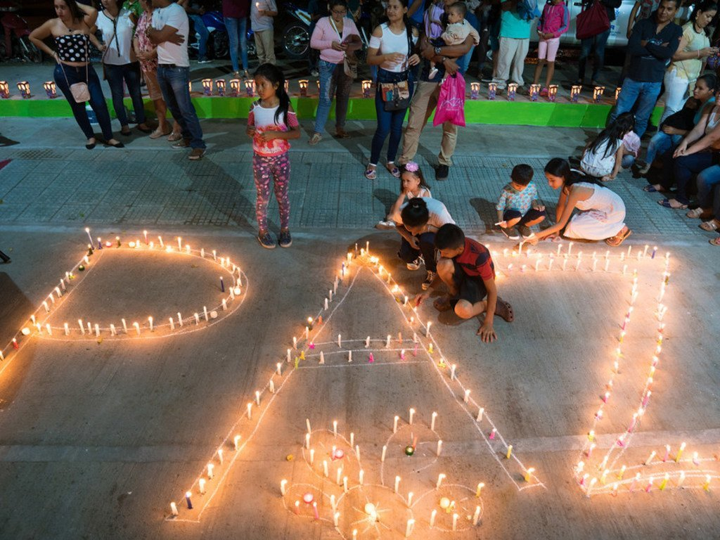 Women and children from the Mocoa community in Colombia light candles forming the word