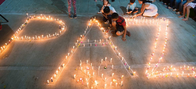 Mujeres y niños encienden velas que forman la palabra paz, en Mocoa, Colombia.