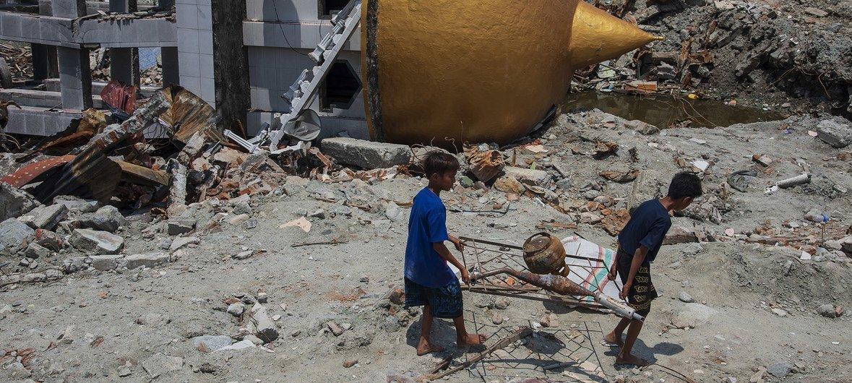Niños en Sulawesi, Indonesia, caminan en una zona destruida después del intenso terremoto ocurrido el 28 de septiembre de 2018.