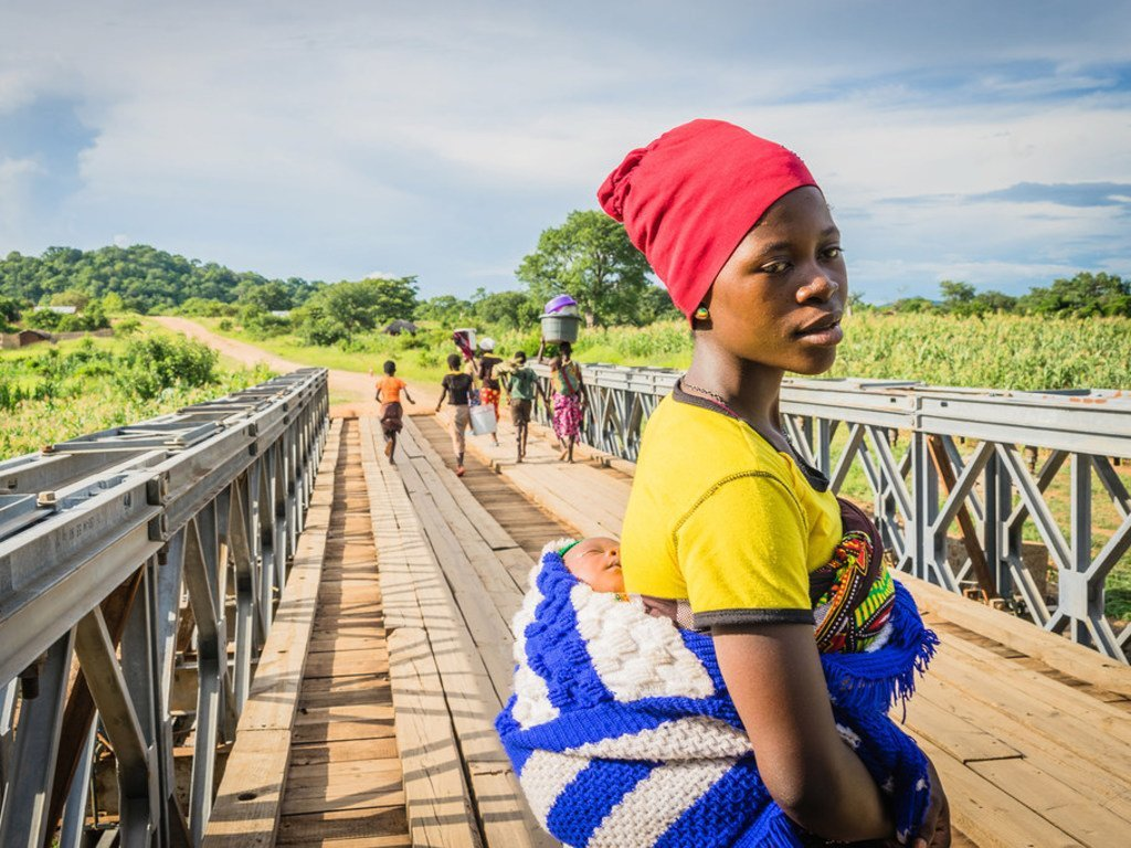 Au Malawi, une femme et son nourrisson traverse un pont pour se rendre au centre de santé Lugola à Chikulo. le pont a été construit grâce à un financement du Programme alimentaire mondial des Nations Unies (PAM)