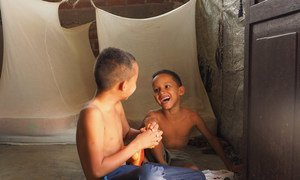 A family of Venezuelans found a new home in Tumbes, Peru, thanks to local solidarity. Here, two children play on the floor of the improvised shelter they are living in.