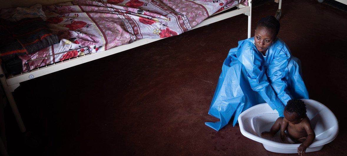 Em Beni, Kavira Langa Jemima, uma sobrevivente do ebola, toma banho Josue, de 6 meses, que está em tratamento para a doença.