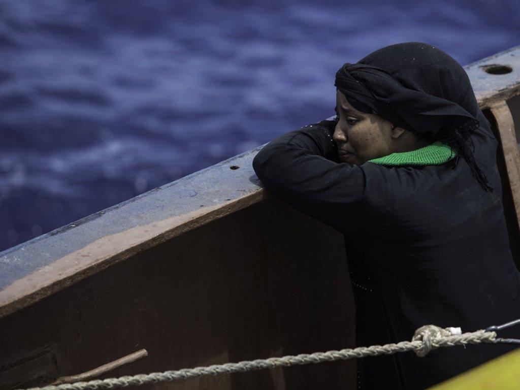 在利比亚,一名妇女被救助船从海上救起后在船舷边哭泣。