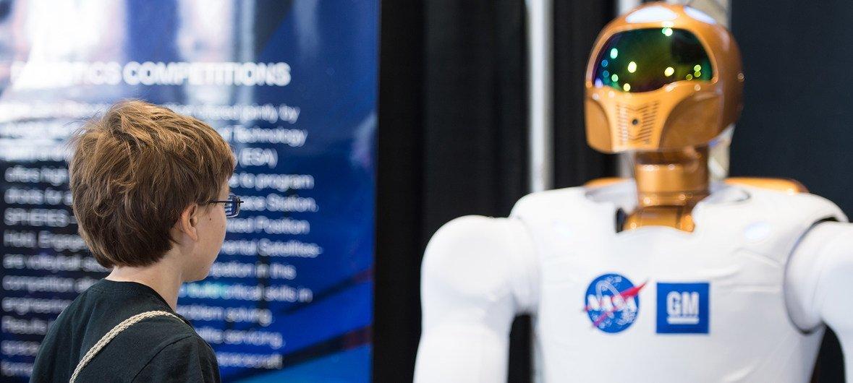 2014年,一位参加美国科学与工程节的来宾,在美国国家宇航局展台近距离观察宇航局研发的第一台Robonaut 2机器人,当时Robonaut 2被安上了1.2米的长腿,以增强灵活性。