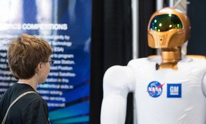 An attendee of the USA Science and Engineering Festival (2014) observes NASA's first dexterous humanoid robot  Robonaut 2, at the NASA Stage. At the time R2 had recently received 1.2 meter long legs to allow mobility.