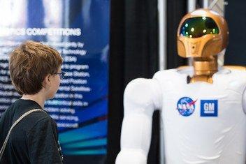زائر في مهرجان العلوم والهندسة بالولايات المتحدة الأمريكية  يتأمل أحد روبوتات وكالة ناسا الفضائية  شديدة التطور وهي بأقدام تساعدها على الحركة.