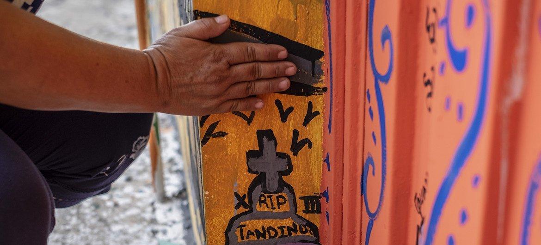 Una madre señala la tumba que pintó en un mural para expresar su dolor por el asesinato de su hijo de 17 años por una pandilla en El Salvador.