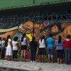 Mujeres centroamericanas que han pedido asilo en México pintan un mural en Tapachula.
