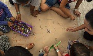 Niños centroamericanos esperan a que se tramiten sus visas humanitarias mientras dibujan en un centro de UNICEF en la frontera entre Mexico y Guatemala