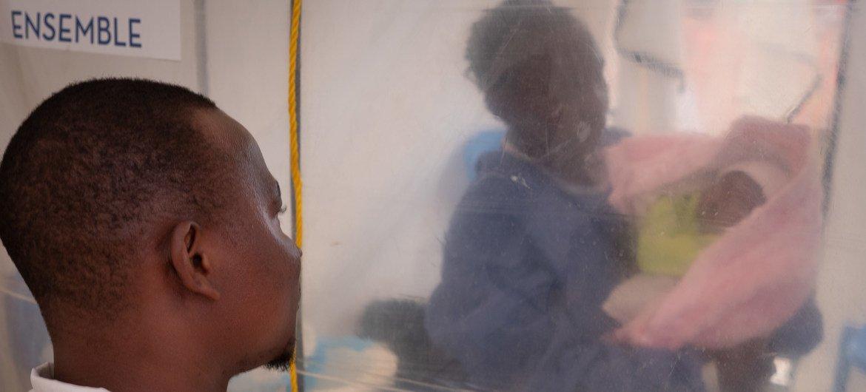 Thomas Kakule Manole observe pendant qu'une survivante d'Ebola s'occupe de sa fille de une semaine, Bénédicte, sous une tente d'isolement dans un centre de traitement Ebola à Beni, dans l'est de la RDC. L'épouse de Thomas est morte du virus Ebola et sa fille, Bénédicte, est également infectée.
