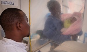 Thomas Kakule Manole observa enquanto um sobrevivente do Ebola se preocupa com sua filha de uma semana, Benedicte, em uma tenda de isolamento em um centro de tratamento de Ebola em Beni