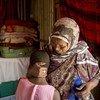 Une femme pratiquant les mutilations génitales féminines avec sa petite-fille âgée de 10 ans, à Diaami, au Somaliland (Somalie). La fillette devait subir une mutilation mais elle est malade à cause d'une infection et sa grand-mère préfère attendre.