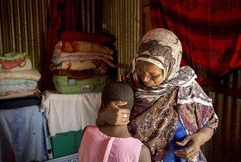 سيدة من اللاتي يقمن بعملية ختان الإناث مع حفيدتها البالغة من العمر 10 أعوام. كان من المفترض أن تخضع الطفلة للختان، ولكنها مصابة بالتهاب، مما جعل جدتها تنتظر شفاها. صوماليلاند..