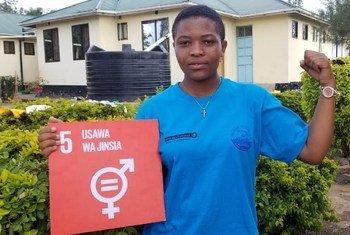 Kijana kutoka Tanzania na bango la lengo namba 5 la malengo ya maendeleo endelevu, SDGs linalotaka usawa wa kijinsia.