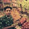A vendor sells produce at his stall in Bangladesh.